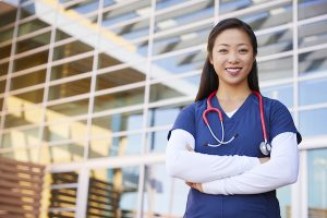 Smiling Asian female healthcare worker with arms crossed